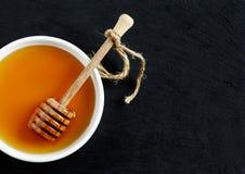Miel y cazo de la miel en fondo negro Fotos de archivo