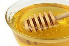 Miel y cazo, tiro macro en el tazón de fuente de cristal Imágenes de archivo libres de regalías