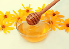 Miel y cuchara de madera adornadas con las flores Foto de archivo libre de regalías