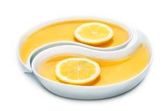 Miel y dos rebanadas de limón en dos bandejas de yang del yin, aisladas encendido Foto de archivo
