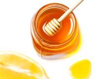 Miel y limón aislados en un fondo blanco Goteo dulce de la miel Foto de archivo