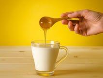 Miele che cade dal cucchiaio di legno in un bicchiere di latte Fotografia Stock Libera da Diritti