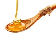 Miele che versa nel cucchiaio di legno Fotografie Stock