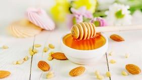 Miele con i favi in un barattolo sui bordi bianchi Immagini Stock Libere da Diritti