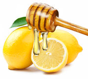 Miele con il bastone di legno che versa su una fetta di limone Fotografia Stock