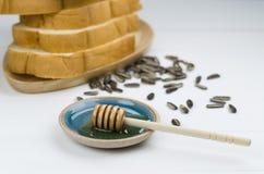 Miele con la pila di semi di girasole e del pane sulla tavola bianca immagine stock