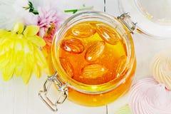 Miele con le mandorle in un barattolo sui bordi bianchi, vista superiore Fotografie Stock
