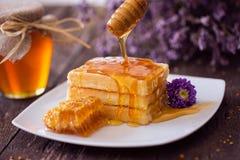 Miele della sgocciolatura da un merlo acquaiolo di legno sulla cialda fresca immagine stock