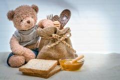 Miele della tazza su tela di sacco con l'orsacchiotto fotografie stock