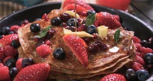 Miele di versamento sopra una prima colazione dei pancake con le bacche Fotografia Stock Libera da Diritti