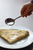 Miele di versamento sul pancake delizioso Fotografie Stock Libere da Diritti