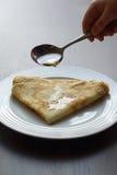 Miele di versamento sul pancake delizioso Fotografia Stock
