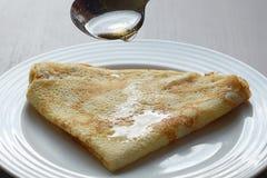 Miele di versamento sul pancake delizioso Fotografia Stock Libera da Diritti