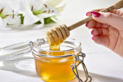 Miele e mano. Jar of honey opened with Dipper and hand Stock Photos