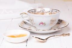 Miele e tazza con tè Immagini Stock