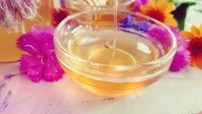 Miele fresco, alimento dolce organico naturale sano del fiore su un fondo concreto grigio video d archivio