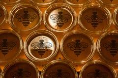 Miele giallo dorato in barattolo di vetro sullo spazio della copia del primo piano del bordo di legno con il logo dell'ape Fotografie Stock