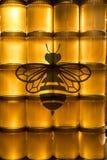 Miele giallo dorato in barattolo di vetro sullo spazio della copia del primo piano del bordo di legno con il logo dell'ape Immagine Stock