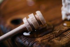 Miele più drizzlier con miele fresco su fondo di legno Immagine Stock