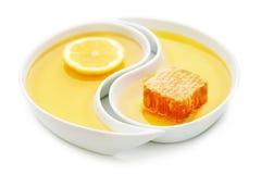 Miele, un favo e una fetta di limone in due vassoi di yin yang, i Fotografia Stock Libera da Diritti