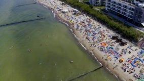 MIELNO, POLONIA - 14 DE JULIO DE 2019 - mosca rápida de la perspectiva aérea del abejón sobre la playa soleada con los turistas d metrajes