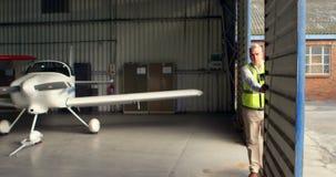 Miembro del equipo que abre la puerta del hangar 4k almacen de video