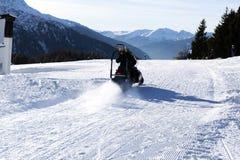 Miembro del personal de la estación de esquí que conduce moto de nieve Estación de esquí en las montañas de Italia Imagen de archivo libre de regalías