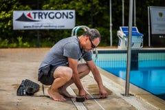 Miembro del personal que coloca la cinta en el lado de la piscina para Measur Imagenes de archivo