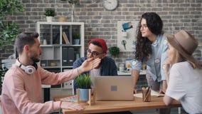 Miembros de equipo que hablan y que gesticulan mirando la pantalla del ordenador portátil en oficina creativa almacen de video
