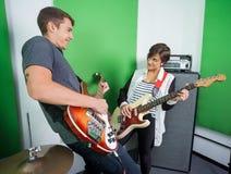 Miembros de la banda que tocan las guitarras en el estudio de grabación fotografía de archivo