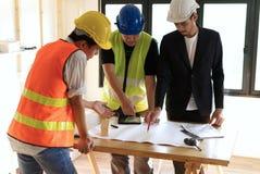 Miembros de la construcción que recolectan en la tabla de funcionamiento que tiene cierta discusión para el planeamiento de pro foto de archivo libre de regalías