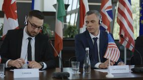 Miembros de la cumbre internacional en auriculares almacen de video