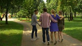 Miembros de la familia contentos que caminan en el parque, disfrutando de fin de semana perfecto junto almacen de video