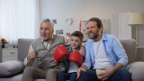 Miembros de la familia emocionados del multiage que animan para el juego de observación del boxeador preferido en la TV almacen de metraje de vídeo