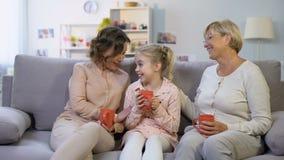 Miembros de la familia femeninos que hablan la sentada en el sofá casero con las tazas de té junta metrajes