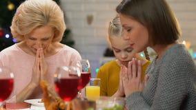 Miembros de la familia femeninos que ruegan antes de cena de la Navidad, tradiciones cristianas metrajes
