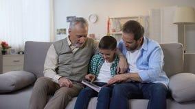 Miembros de la familia de Multiage que miran el photoalbum, límites fuertes de la familia, unidad almacen de metraje de vídeo