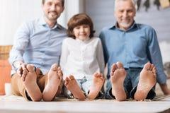 Miembros de la familia positivos felices que se sientan junto Imágenes de archivo libres de regalías