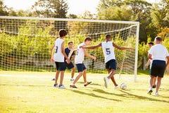 Miembros del fútbol masculino de la High School secundaria que juega el partido Imágenes de archivo libres de regalías