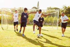 Miembros del fútbol masculino de la High School secundaria que juega el partido Fotografía de archivo