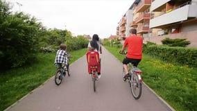 Miembros del tiempo feliz del gasto de la familia junto al aire libre Se divierten mucho que monta en las bicis almacen de video