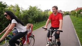 Miembros del tiempo feliz del gasto de la familia junto al aire libre Se divierten mucho que monta en las bicis metrajes