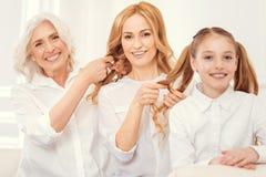 Miembros femeninos de emisión de la familia que trenzan el pelo junto Foto de archivo libre de regalías