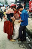 miembros locales de la tribu del hmong de la flor que embalan un poco de granos y producción a un saco plástico grande en el merc fotografía de archivo