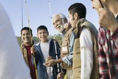 Miembros masculinos con la sonrisa de las cañas de pescar Imagenes de archivo