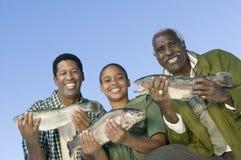 Miembros masculinos de la familia que muestran pescados Imagen de archivo