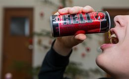 Teenage boy drinks Hell energy drink. royalty free stock images