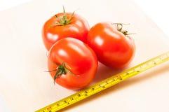 Mierzy kalorie trzy czerwonego pomidoru z centymetrem Fotografia Royalty Free