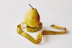 Mierzy taśmy i świeżej owoc bonkrety na białym tle Strata ciężar, szczupły ciało, zdrowej diety pojęcie obrazy stock