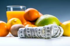 Mierzy taśmy i świeżej owoc w tle obrazy stock